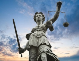 justice statue with sword and scale. cloudy sky in the background